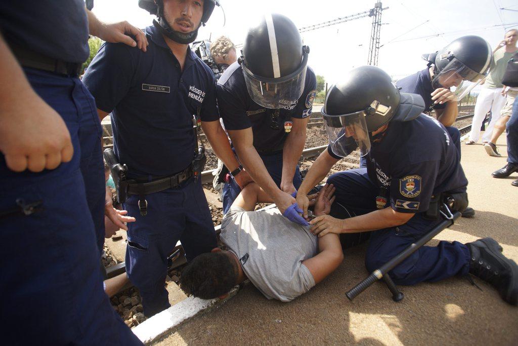 Bicske, 2015. szeptember 3. Rendõrök lefognak egy férfit a bicskei vasútállomáson, ahol leszállították az illegális bevándorlókat a Budapestrõl Sopronba tartó vonatról 2015. szeptember 3-án. MTI Fotó: Balogh Zoltán